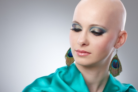 Beauty portrait of bald woman in turquoise silk dress  65533; photo