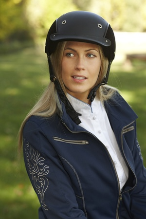 Outdoor portrait of attractive female rider in equestrian helmet, looking away. photo