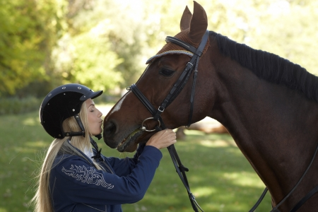 be kissed: Female rider kissing horse, outdoor photo. Friendship between rider and horse. Stock Photo