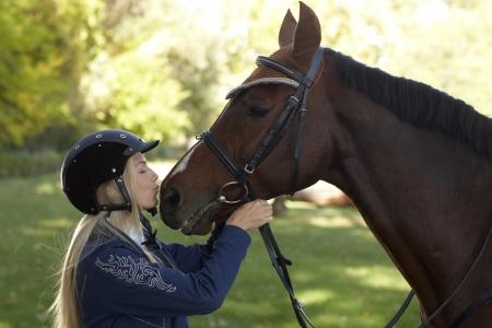 mujer en caballo: Mujer jinete caballo besos, foto al aire libre. La amistad entre jinete y caballo. Foto de archivo