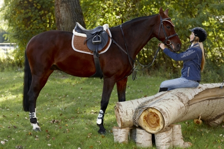 Horse and pretty female rider taking a break in the woods.