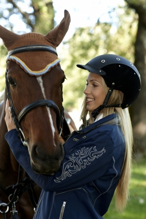 Pretty female rider embracing horse outdoors. photo