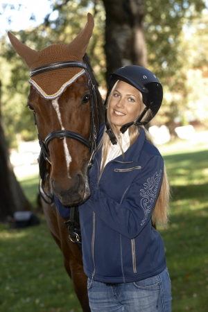 Pretty female rider embracing horse outdoors, smiling happy at camera. photo
