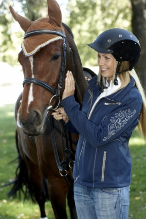 Female rider in equestrian helmet caressing horse, smiling. photo