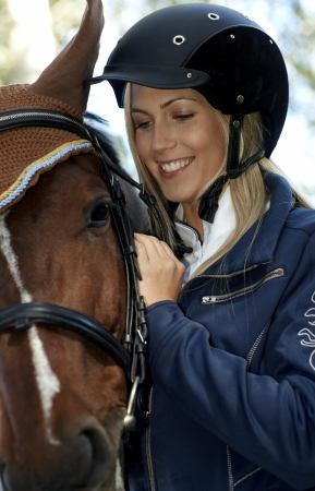 Closeup outdoor portrait of female rider and horse embracing. photo