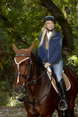 Pretty blonde girl horseback riding in the woods. photo