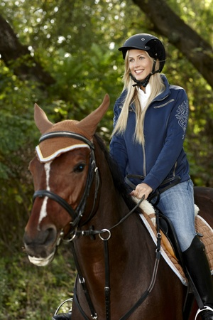 Happy blonde woman horse riding in the forest. photo