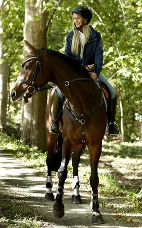 parapente: Joven jinete a caballo rubia mujer a caballo en el bosque. Foto de archivo