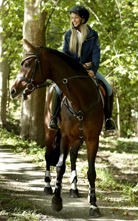 free riding: Young blonde female rider horseback riding in the woods. Stock Photo