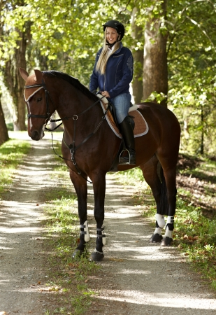 Horse and attractive female rider in the forest, rider smiling happy.