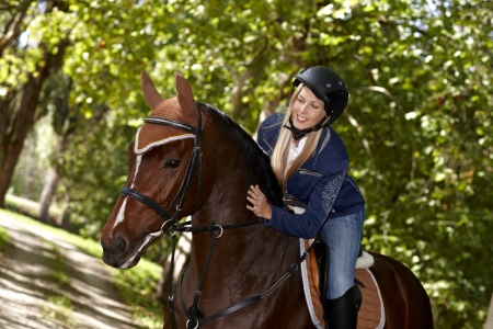 Attractive female rider caressing horse while riding in the woods. photo