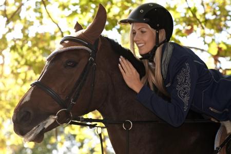 Foto del primer del jinete femenino atractivo inclinado sobre caballo, sonriendo feliz.