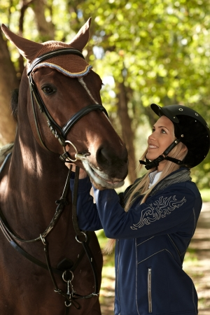 Young female rider looking at horse with love, outdoor photo. photo
