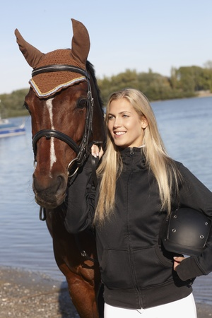 bridle: Portrait of young blonde female rider and horse at riverside. Stock Photo
