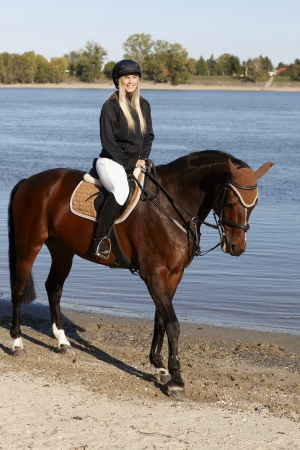 animal photo: Horse and young female rider at riverside.