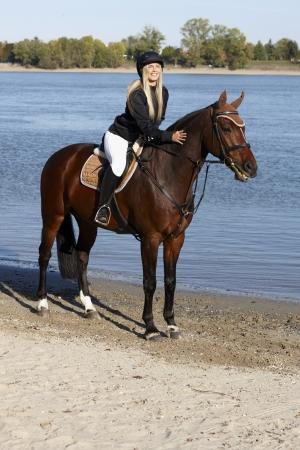 full size: Blonde female rider sitting on horse, caressing, smiling. Stock Photo