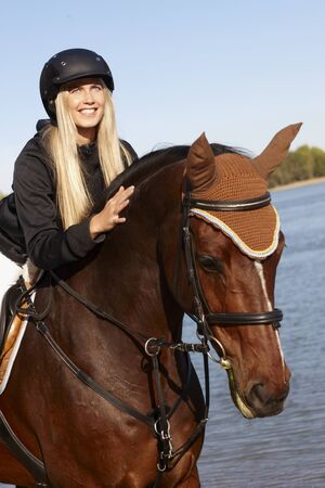 Closeup photo of young female rider leaning over horse at riverside. Stock Photo - 17369426