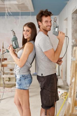 Feliz pareja joven de pie espalda con espalda celebración de taladro de la energía en el hogar renovado.