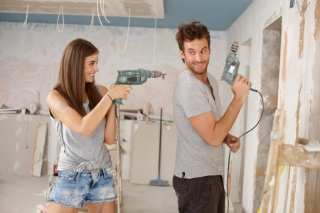 Happy young couple having fun during renovation, playing with power drill. photo