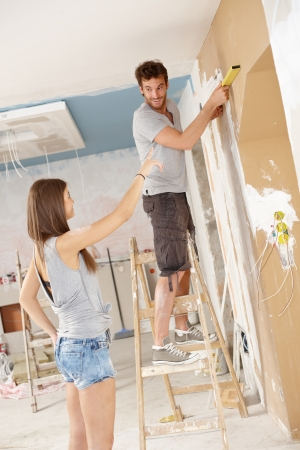 Young couple renovating home, DIY, measuring. photo