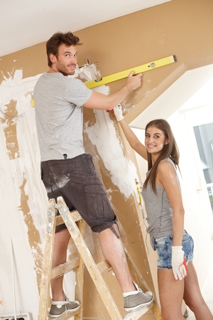 spirit level: Attractive young couple building new home using spirit level to measure.