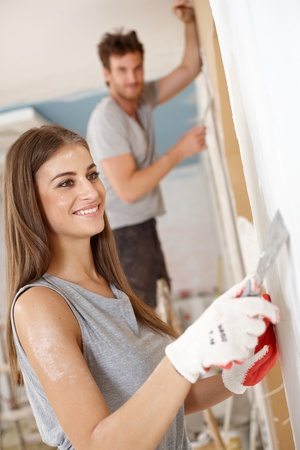 Attractive young woman renovating house, boyfriend at background.