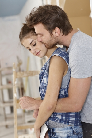 Loving couple embracing and kissing while renewing flat. photo