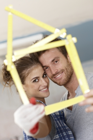 folding camera: Happy young couple smiling through little house formed by ruler, DIY.