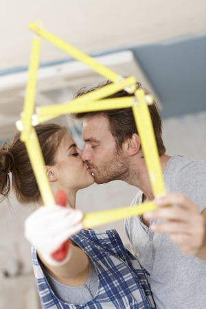 Kissing couple forming little house of ruler, renewing home. photo
