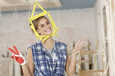 home made: Happy woman building a new home, DIY, little house made of ruler framing her face. Stock Photo