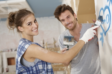 man painting: Romantic couple renovating house, painting heart on wall, smiling happy. Stock Photo