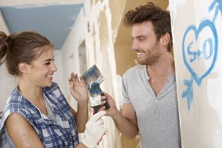Loving couple having fun at home renovation, painting, DIY. Stock Photo - 17418190