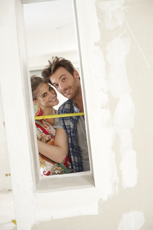 Happy couple DIY at home renovation, smiling, looking through window. photo