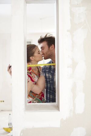 renewing: Young couple renewing home, kissing, measuring   65533;