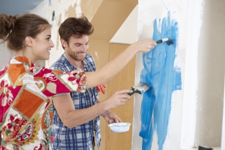 Happy young couple renewing home, painting wall to blue, smiling happy   65533; photo