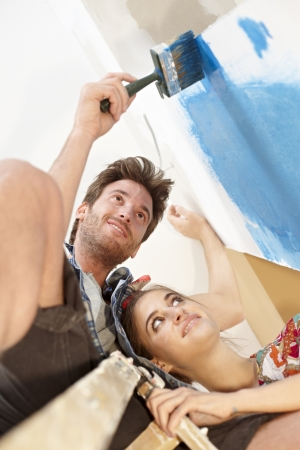 Happy young couple painting wall, renovating home, smiling  Man on top of ladder  Below view   65533; photo