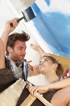Loving couple DIY painting wall to blue at home, man on top of ladder  View from below   65533; photo