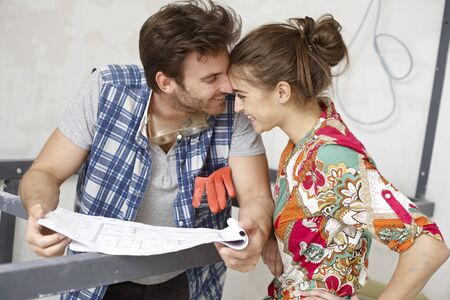 improving: Happy couple with floor plan, DIY, renewing home   65533; Stock Photo
