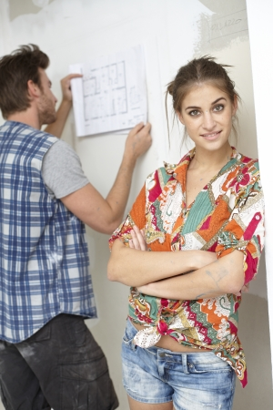 Young couple planning new home, man looking at floor plan, woman standing arms crossed, smiling   65533; Stock Photo - 17423456