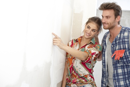 Young couple examining painting in new home under construction   65533; photo