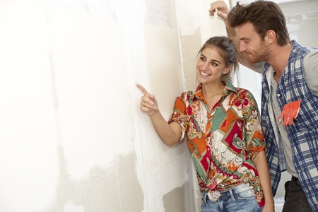 Happy couple examining painting in new house under construction. photo