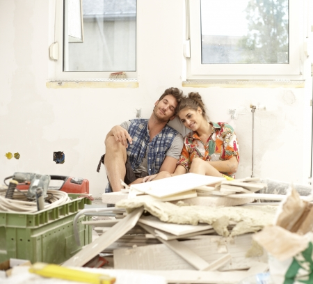 renovating: Young couple sitting exhausted in house under construction among construction waste, smiling.