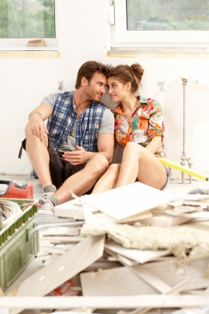 Young couple sitting on floor in house under construction among construction waste, smiling   65533; photo