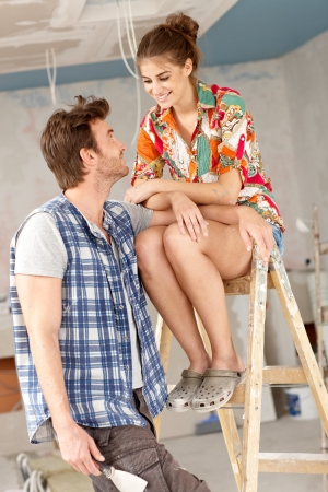 renewing: Young couple renewing home, woman sitting on top of ladder, smiling   65533;