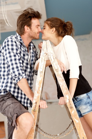 be kissed: Loving couple kissing on ladder in house under construction   65533;