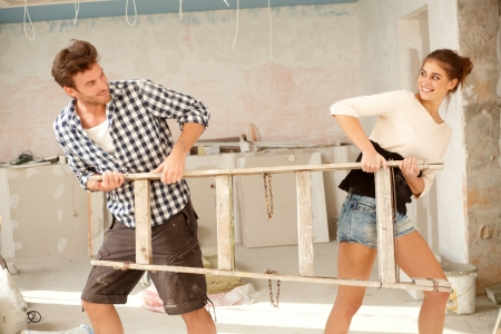 Young couple pulling ladder to opposite directions in house under construction, having fun   65533; photo