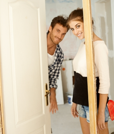 Young couple looking through door-case in new home under renovation   65533; photo