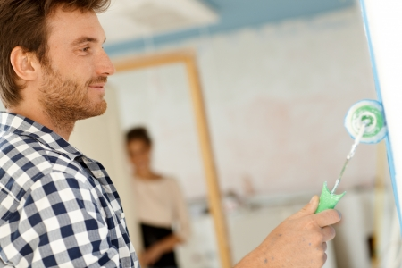 man painting: Happy young man painting wall in house under construction   65533; Stock Photo