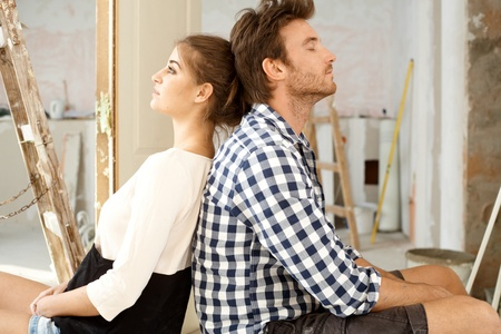 renewing: Young couple sitting on floor exhausted in renewing house  Sitting back to back   65533;