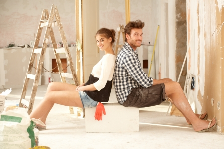 Happy young couple sitting happy in home under construction   65533; Stock Photo - 17423429
